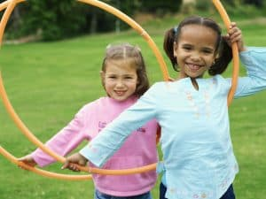 two girls playing with plastic hoops