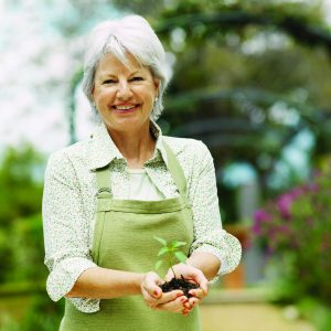 older woman holding a plant in cupped hands