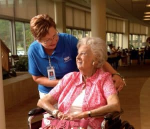 staff member pushing patient in wheelchair