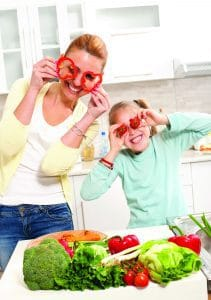 mom and daughter in kitchen, making funny faces with vegetables in front of face