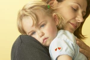 Mother consoling sick daughter