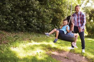 Father Pushing Children On Tire Swing
