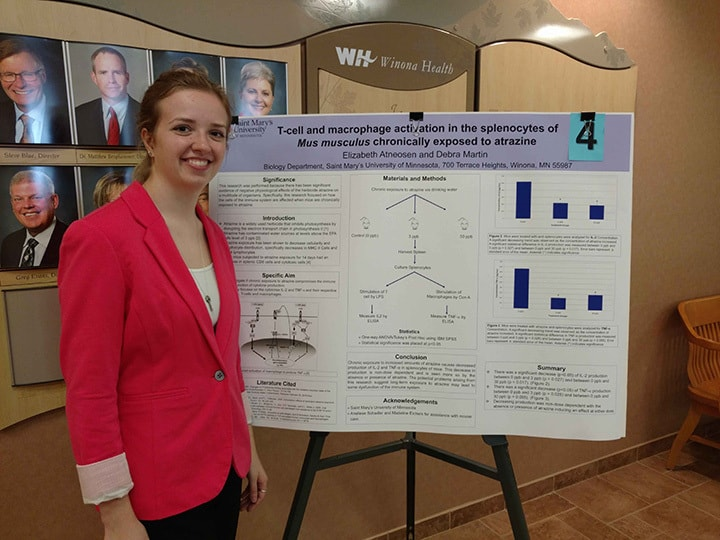 WSU student poses with her project at Winona Health's 2018 Student Research Fair.
