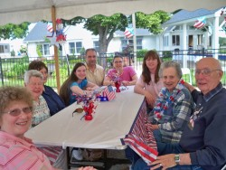 Residents and families enjoy a picnic and entertainment in the courtyard at Adith Miller and Roger Metz manors.