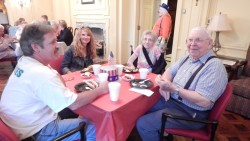 Residents and families gather for dinner and entertainment during Senior Living at Watkins' annual family picnic.